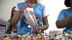 Voluntários de igreja preparam doces para distribuir aos fiéis no Guará