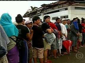 Tufão deixa cidades devastadas e filas de moradores nas Filipinas - A fila de pessoas tentando deixar a cidade de Tacloban não tem fim. O que chama a atenção é a quantidade de sujeira e destroços espalhados por todos os lugares, além do choro das crianças.