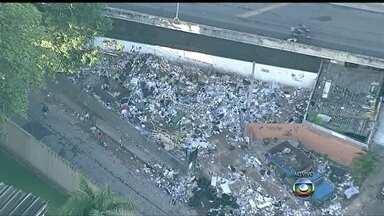 Lixo toma conta de viaduto em Madureira - A 500 metros da entrada do Túnel Noel Rosa, o lixo toma conta do ambiente. Um caminhão está descarregando os resíduos. Pneus acumulam água e atraem animais.