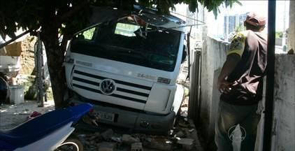 Caminhão carregado de pedras bate em muro de casa no bairro Altiplano, em João Pessoa - Árvore impediu que veículo entrasse ainda mais no local.