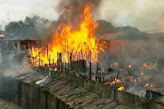 Incêndio destrói 70% das casas de favela na Zona Leste - Vinte e seis equipes de bombeiros foram mobilizadas para combater o fogo que atingiu a favela Aracati, na Penha. As chamas chegaram perto, mas não interromperam o trânsito no Viaduto Engenheiro Alberto Badra.