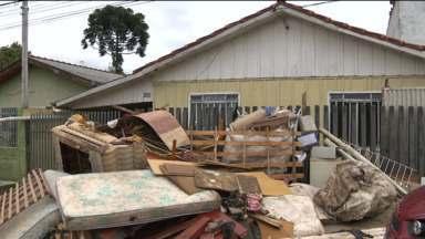 Depois da chuva, é hora de limpar os locais mais afetados com a enchente - Na região da CIC, um dos bairros mais atingidos, caminhões saem lotados com objetos perdidos pelos moradores por causa da chuva