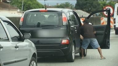 Bandidos aproveitam engarrafamento para tentar assaltar família em São Paulo - O motorista levou um soco. Em seguida, um bandido tentou arrancar a bolsa da mulher que estava no banco do passageiro. O homem que dirigia saiu com o carro e o ladrão, que estava com uma pistola, saiu andando pela rodovia. Ninguém se feriu.