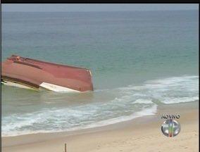 Apesar de interdição na praia banhistas nadam próximo a traineira encalhada em Maricá, RJ - Embarcação está no local há uma semana.