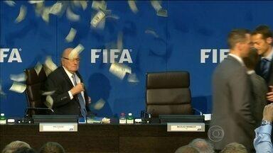 Blatter é recebido com protesto antes de coletiva sobre eleições da Fifa - Comediante joga dinheiro na direção do presidente da entidade.