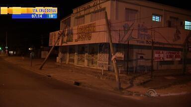 Postes caídos em cima de prédio são de telefonia - Postes estão inclinados e escorados em academia de ginástica em avenida de Porto Alegre.
