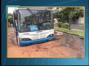 Ônibus fica 'enroscado' após cair em buraco no bairro Humberto Salvador - Veículo passava pela Avenida João Domingos.