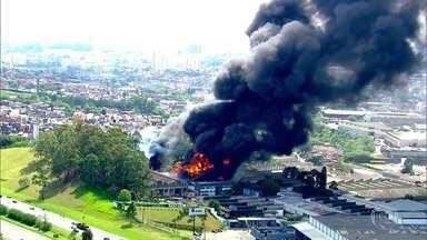 Bombeiros controlam fogo em galpão de empresa de cosméticos na Grande São Paulo - Oito pessoas ficaram feridas no incêndio que atingiu o galpão de uma fábrica de perfumaria e cosméticos na Rodovia dos Imigrantes, na região de Diadema.
