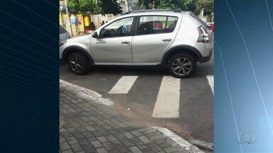 Motoristas param em locais proibidos e atrapalham o trânsito em Goiânia - Foto mostra veículo estacionado na faixa de pedestre e em uma curva.