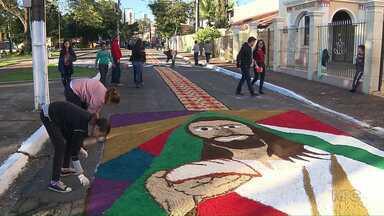 Fiéis e voluntários acordaram cedo para montar os tradicionais tapetes de Corpus Christi - Imagens foram desenhadas com pó de café, serragem e papel.