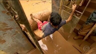 Pintor se arrisca em contato com a lama em cidade de MG - Sobe para 4 o número de mortos nos temporais que atingiram Minas.