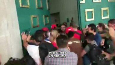 Professores e funcionários da rede estadual de ensino ocupam entrada do Palácio Iguaçu - Tropa de Choque da PM chegou ao local por volta das 13h para acompanhar a situação. Categoria pede reunião com o governo e deve ser recebida na terça-feira (19).