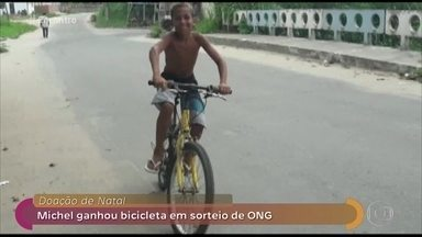 Projeto recicla bicicletas para doar a catadores de lixo - Fátima conversa com menino que foi um dos presenteados no sorteio da ONG