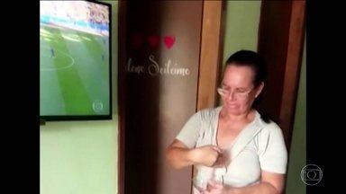 Saiba quem é dona Dinha, mulher que salvou o Brasil contra a Costa Rica - É ela que aparece no vídeo que se espalhou pela web carregando uma vela para baixo do aparelho de TV, segundos antes do gol de Philippe Coutinho.