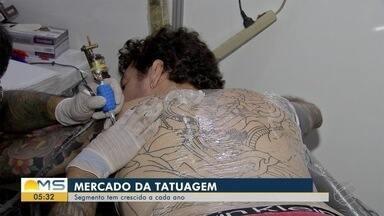 Mercado da tatuagem tem crescido a cada ano - De acordo com o Sebrae, nos últimos dois anos, o mercado da tatuagem cresceu quase 25% no Brasil. Hoje em dia, é grande o número de pessoas que tem pelo menos um desenho tatuado no corpo. Mas será que a tatuagem atrapalha na hora de arranjar um emprego?