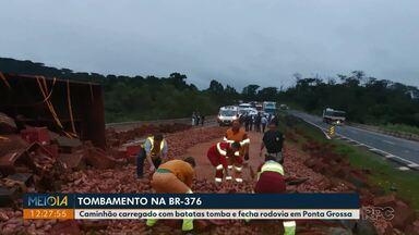 Caminhão carregado com batatas tomba e fecha rodovia em Ponta Grossa - A carga ficou toda espalhada pela rodovia. Funcionários da concessionária que administra o trecho passaram a manhã limpando o local.