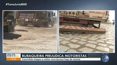 Buraqueira prejudica motoristas na BR-324, entre os bairros de Valéria e Palestina - Caminhão ficou preso em buraco na marginal da rodovia na manhã desta quinta-feira (1º).