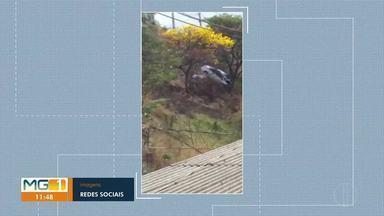 Carro fica pendurado ao cair em barranco, em Caratinga - Uma árvore parou o veículo.