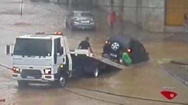 Carro cai em buraco na avenida Expedito Garcia, em Cariacica, ES - Rua estava alagada.