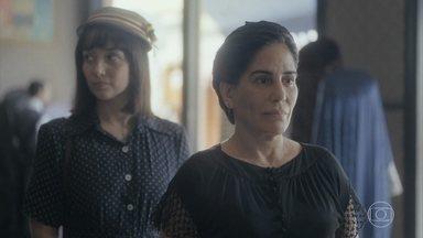 Lola procura Assad na loja, que a convida para ir até o escritório - Clotilde, que acompanhava a irmã, decide ficar no salão por causa de Almeida
