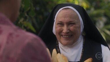 Lola volta da padaria e entrega pães para Madre Joana - A Madre agradece a doação e a convida para visitá-la com mais calma outro dia