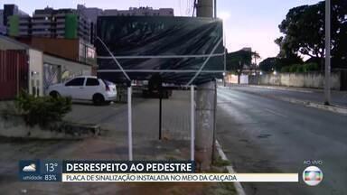 Placa é instalada no meio da calçada em Taguatinga - Sinalização fica entre uma grade e a rua, não sobra espaço para pedestre.