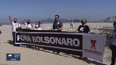 Sindicalistas colocam cruzes em praia de Santos como protesto por mortes - Protesto aconteceu para chamar a atenção sobre mortes causadas pela Covid-19.