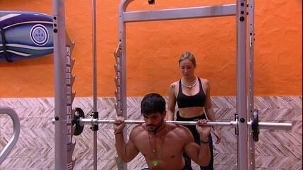 Jéssica ajuda Lucas em exercício de agachamento