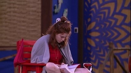 Ana Clara lê sozinha na área externa