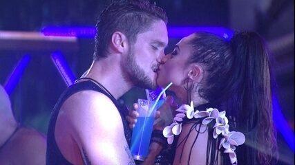 Paula e Breno cruzam os braços com seus drinks e se beijam