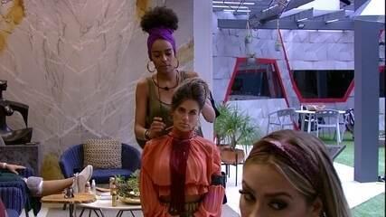 Gabriela tenta fazer coque no cabelo de Carolina