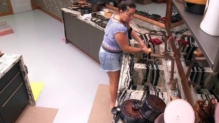 Tereza lava louça na cozinha