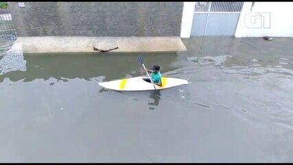 Homem usa caiaque para se locomover em rua alagada em Paulista