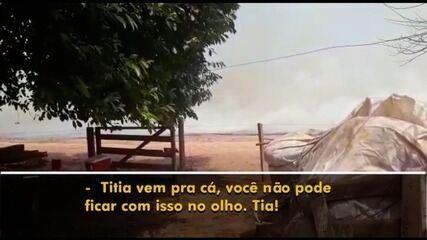 Criança tenta acalmar tia que se desespera com chegada do fogo próximo a casa, em Edeia