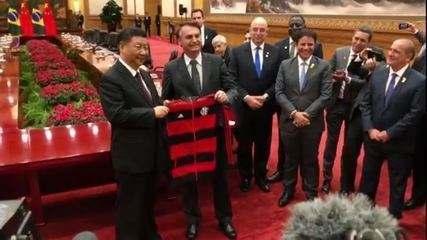 Bolsonaro diz que '1,3 bilhão de chineses serão Flamengo' em novembro e dá agasalho do clube a Xi Jinping