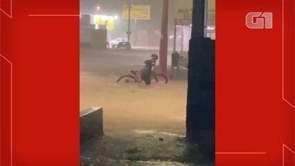 Ciclista 'encara' enxurrada em bairro de Campo Grande e leva tombo na rua: 'Eu queria cheg
