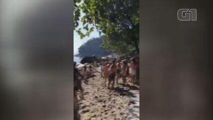 Dezenas de pessoas invadem praia com acesso bloqueado em Guarujá, SP