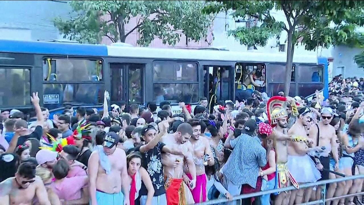 Foliões cercam e invadem ônibus em rua lotada no bloco Agrada Gregos, em São Paulo