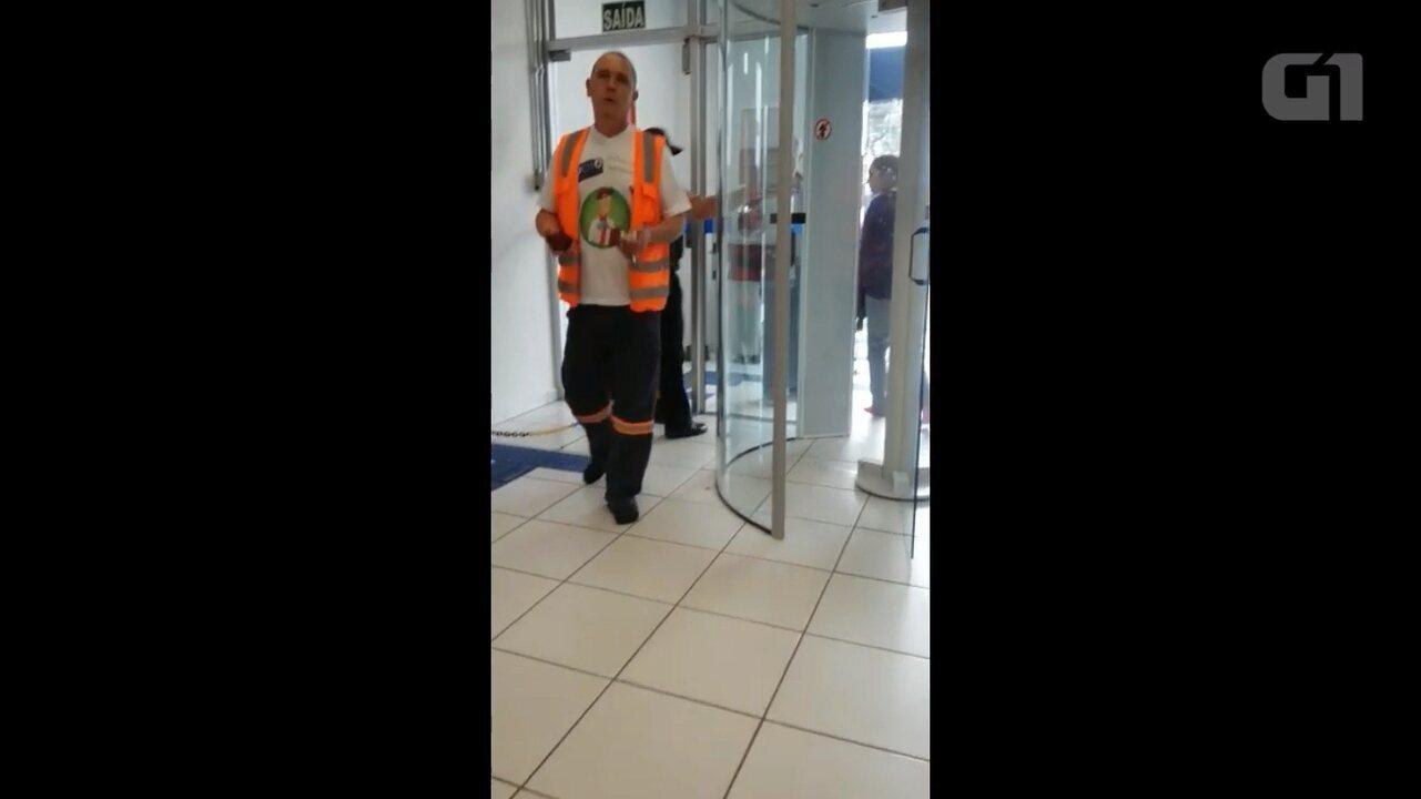 Clientes são barrados em porta giratória e entram de meias em agência bancária