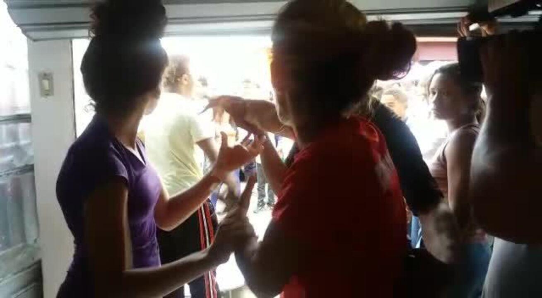 Mãe (de vermelho) se nega a enterrar filha morta por acreditar que ela ainda está viva