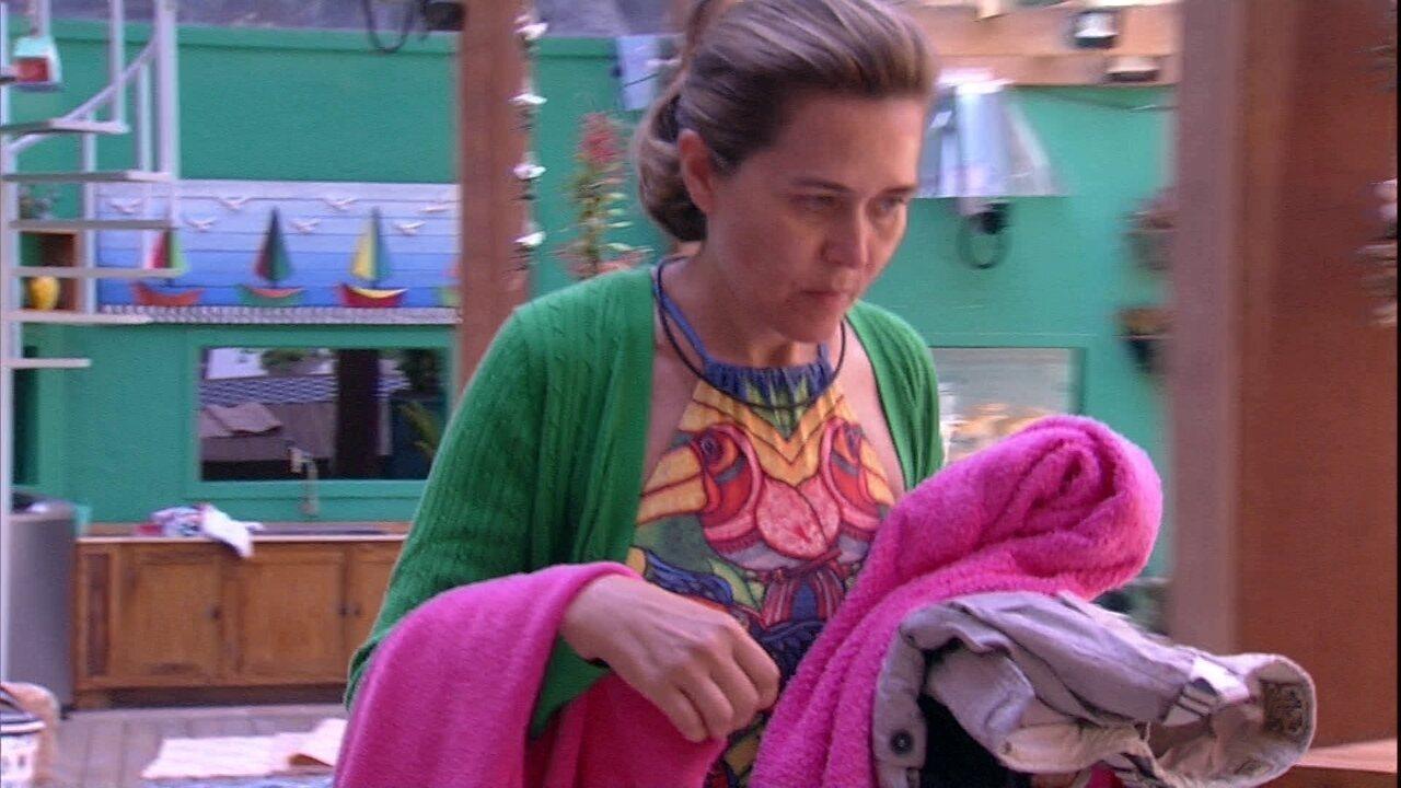 Eva recolhe as roupas da área externa