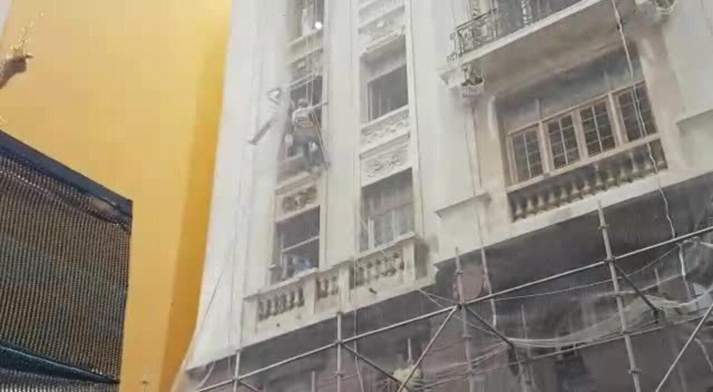 Trabalhadores em andaime dançam na passagem de bloco no Centro de SP