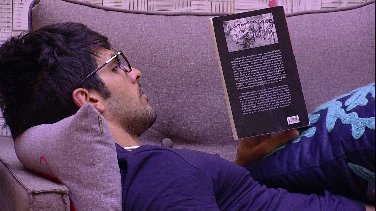 Lucas lê um livro sozinho na sala