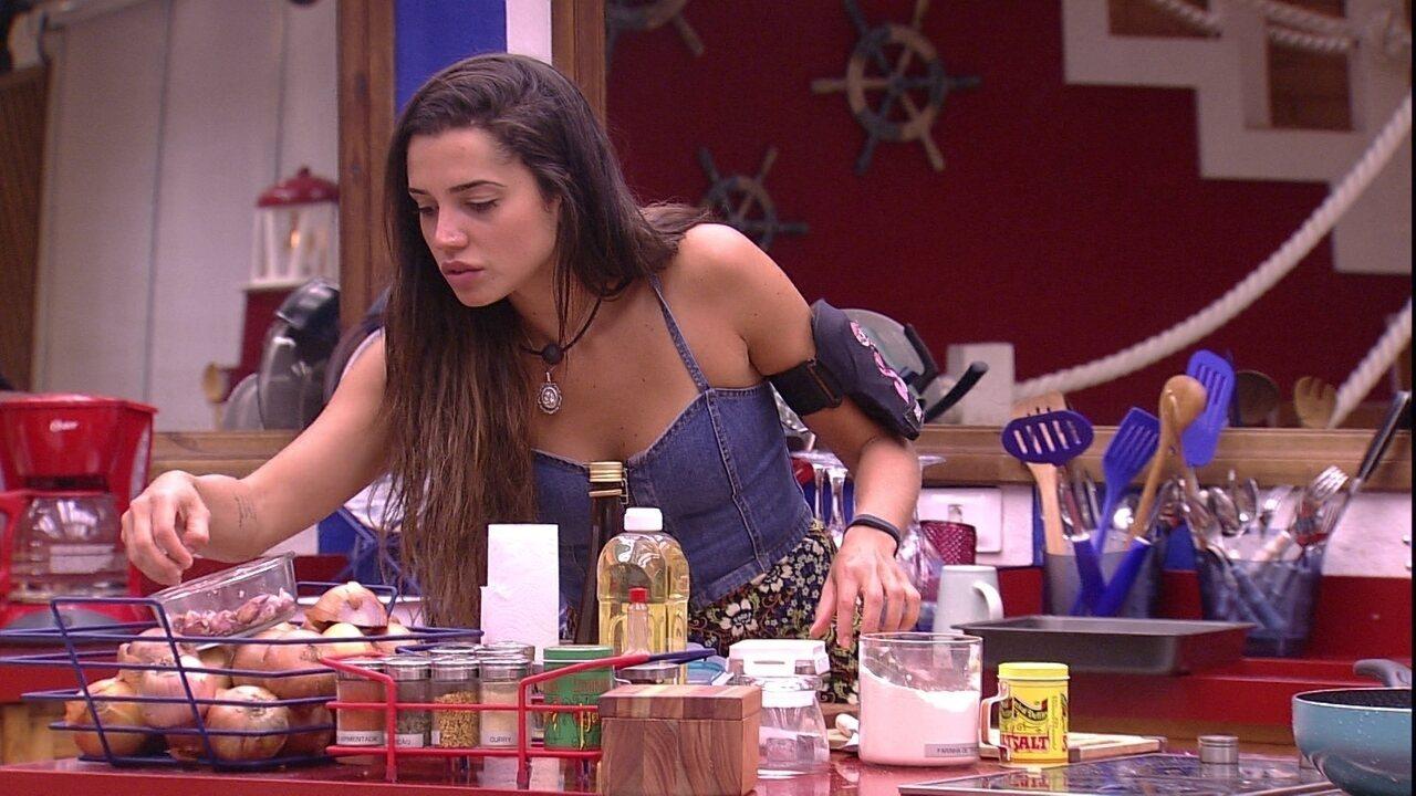 Paula descasca alho para preparar o almoço