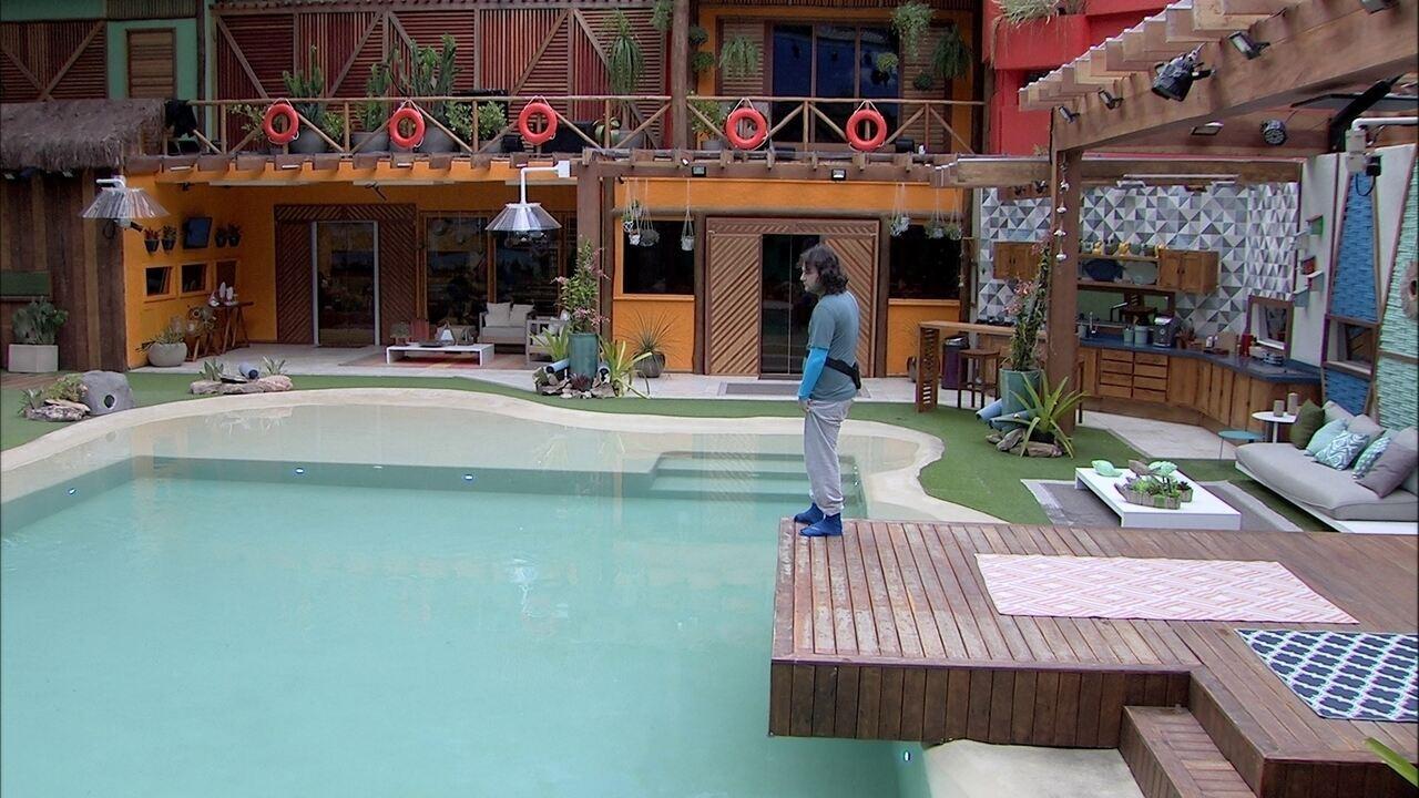 Diego observa piscina na área externa