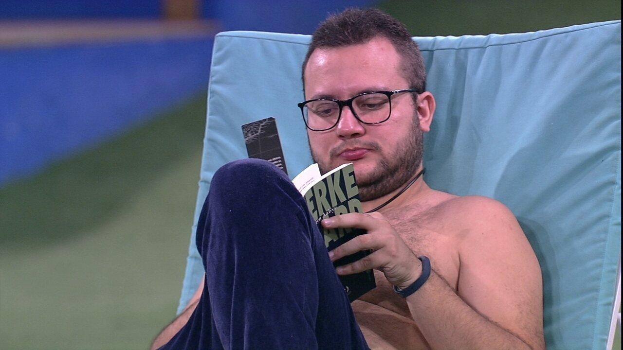 Diego lê um livro na beira da piscina