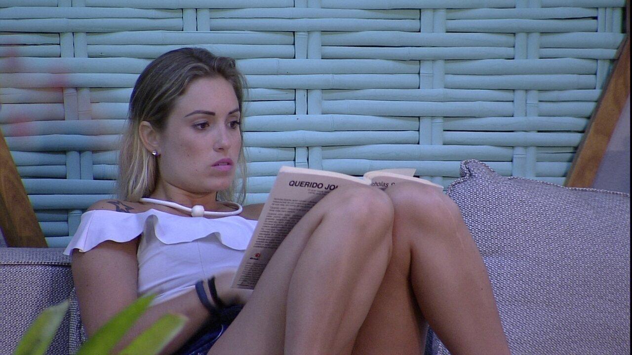 Jéssica e Ana Clara lêem no sofá do deck