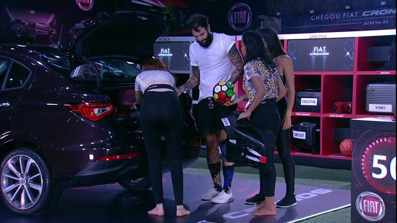 Participantes organizam itens no porta-mala do carro Vermelho Marsala