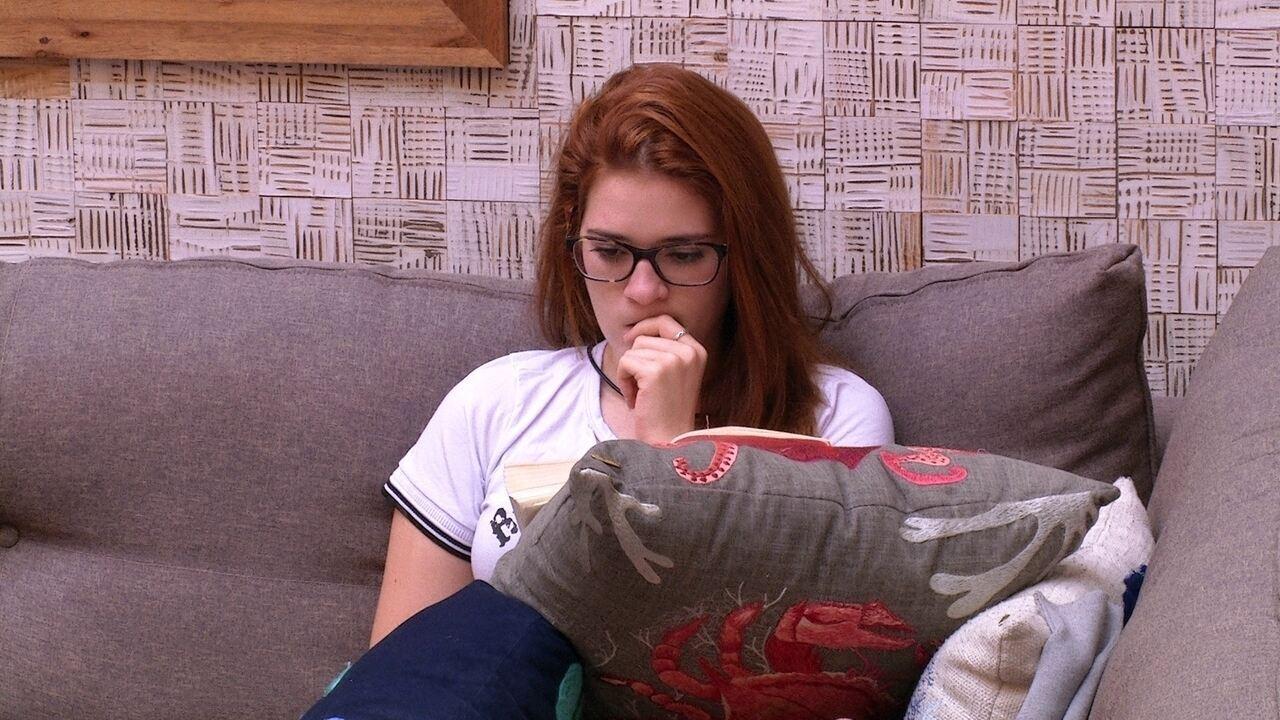 Ana Clara lê um livro no sofá