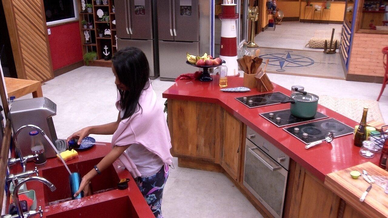 Gleici lava garrafas de água na cozinha